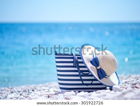 bag and hat on beach - stock photo