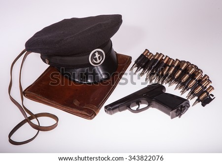 Bag cards, pistol and naval cap on a white background in studio for maps and a gun on a white background in studio - stock photo