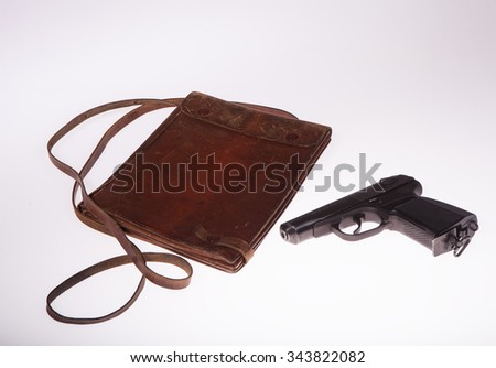 Bag for maps and a gun on a white background in studio - stock photo