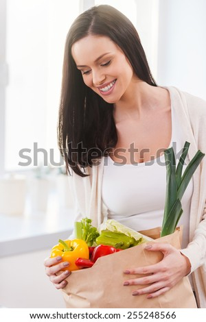 Bag full of health and colors. Beautiful young woman unpacking shopping bag full of fresh vegetables and smiling while standing in the kitchen - stock photo