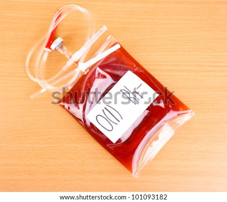 Bag of blood and infusion on wooden background - stock photo