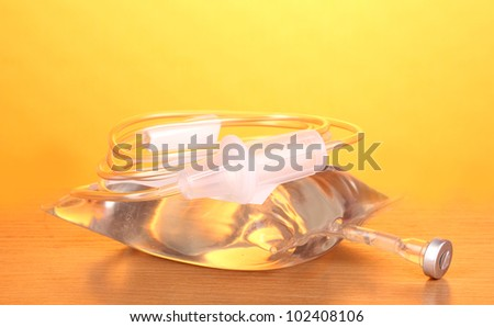 Bag of intravenous antibiotics and plastic infusion set on wooden table on yellow background - stock photo
