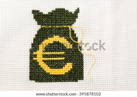 Bag of money with euro symbol embroidered green and yellow thread on white fabric. - stock photo