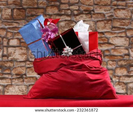Bag of Santa Claus with Christmas and New Year gifts on red table on blurred stone wall background  - stock photo