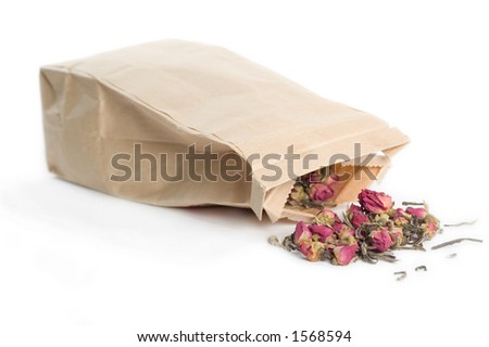 Bag of tea with tea spilled out.  Isolated on white. - stock photo