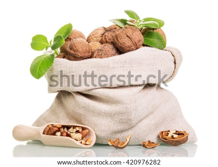 Bag of walnuts, and a scoop with kernels isolated on white background. - stock photo