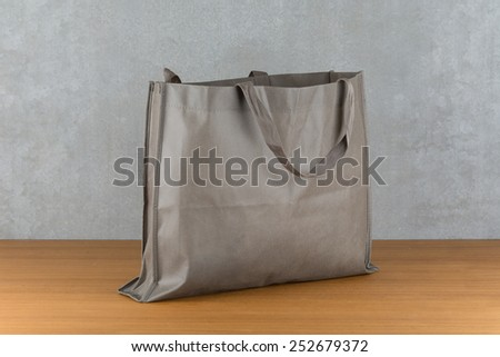 bag on wood table and ciment background - stock photo