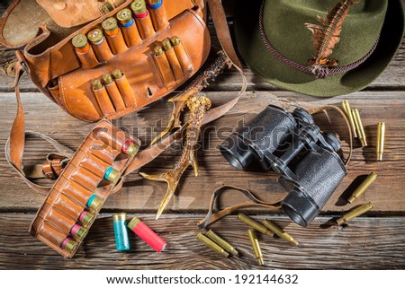 Bag with bullets, binoculars and hat in a hunting lodge - stock photo