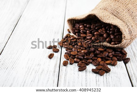 Bag with coffee  beans on a old wooden table