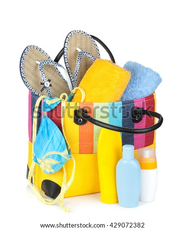 Bag with towels, sunglasses, flip-flops and beach items. Isolated on white background