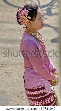 BAGAN, MYANMAR - CIRCA FEBRUARY 2007: Woman in a fine pink sarong and traditional dress in a Buddhist procession