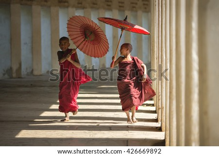 BAGAN, MYANMAR - DEC 6: Unidentified two young Buddhism novice is running and holding an umbrella at Shwezigon temple on Dec 6, 2014 in Bagan.  - stock photo