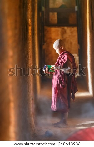BAGAN, MYANMAR - DEC 6: Unidentified young Buddhism novice pray at Shwezigon temple on Dec 6, 2014 in Bagan. Buddhism is predominantly of the Theravada tradition, practised by 89% of the population. - stock photo