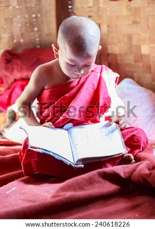 BAGAN, MYANMAR - DEC 6: Unidentified young Buddhism novice read the book on Dec 6, 2014 in Bagan. Buddhism is predominantly of the Theravada tradition, practised by 89% of the population. - stock photo