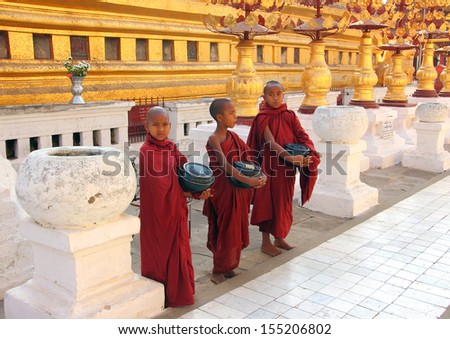 BAGAN, MYANMAR - FEBRUARY 16, 2013: Three young buddhist monks are standing in the famous Shwezigon Pagoda, Bagan, collecting money. - stock photo