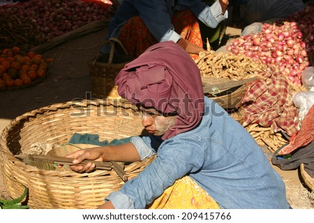 BAGAN, MYANMAR:  JAN. 1:  A Burmese woman sells produce at an outdoor market on January 1, 2010 wearing thanaka, a cosmetic paste made from bark and used as sunscreen and insect repellent. - stock photo