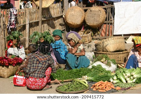 BAGAN, MYANMAR:  JAN 1:  Local women sell their produce at an outdoor market in Bagan on January 1, 2010. The markets operate daily and are a gathering spot for sales and gossip.  - stock photo