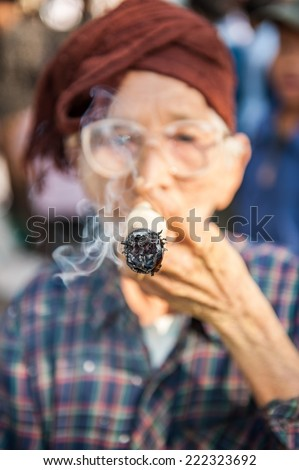 Bagan,Myanmar-March 18,2011: An unidentified woman smoking a cheroot cigar in market in bagan, Myanmar . A cheroot is a cigar made principally by dried fruits and little bit of tobacco.