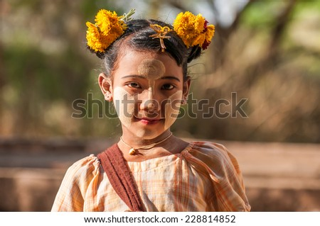 Bagan,Myanmar-March 18,2011: Unidentified Myanmar girl with thanaka on her smile face is happiness in Bagan, Myanmar.Thanaka is a yellowish-white cosmetic paste made from ground bark. - stock photo