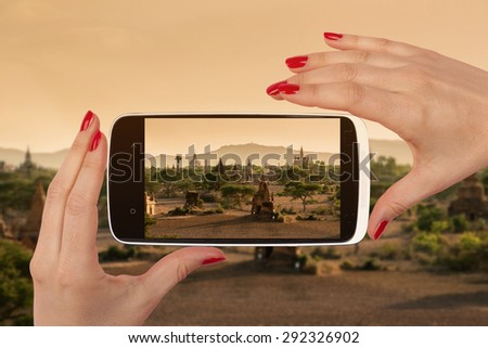 Bagan snapshot on smartphone screen in female hands with red nails. Female travel, vagabonding and backpacking.  - stock photo