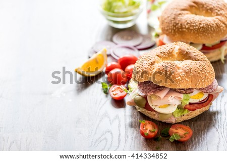 Bagel sandwich with turkey breast,served on wooden board,selective focus and blank space - stock photo