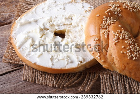 Bagel with cream cheese and sesame close-up on a wooden table. horizontal view from above  - stock photo