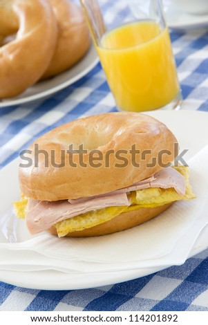 Bagel with egg and ham filling on a breakfast table