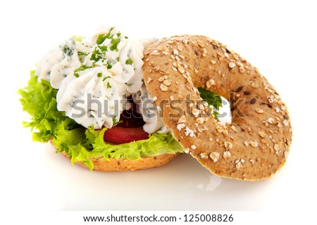 Bagel with fresh cream cheese and fresh herbs isolated over white background - stock photo