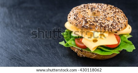 Bagel (with Gouda cheese) on vintage looking background (close-up shot; selective focus)