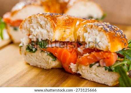 Bagel with salmon and arugula - stock photo