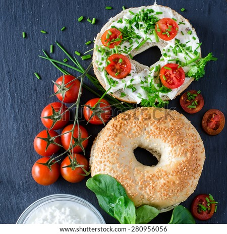 Bagels sandwiches with cream cheese, tomatoes and chives for healthy snack copy space - stock photo
