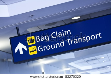 Baggage claim and ground transport sign hanging from ceiling at the airport