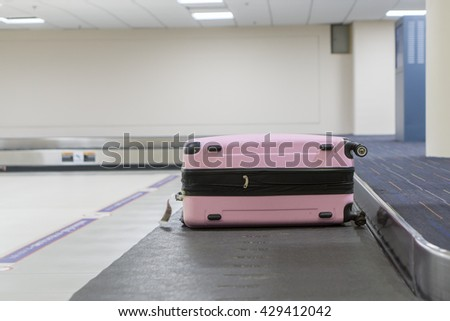 Baggage claim at the airport,suitcases on a luggage band on the airport,Baggage on conveyor belt at the airport - selective focus,vintage color - stock photo