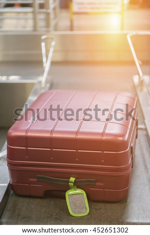 Baggage claim  suitcases on a luggage band on the  on conveyor belt at the airport - selective focus,vintage color - stock photo