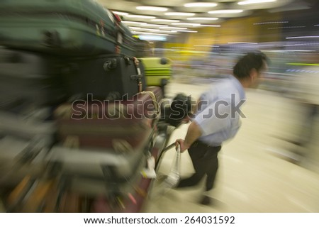 Baggage man pulls luggage at Madrid Barajas Airport (MAD), Spain's busiest airport - stock photo