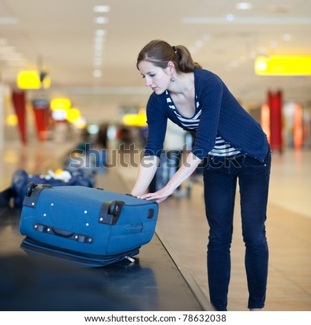 Baggage reclaim at the airport - pretty young woman taking her suitcase off the baggage carousel