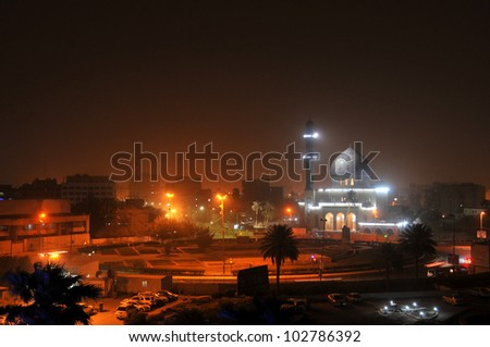 Baghdad by night. Shahid Mosque (where sunni muslims worship) at Firdos Square in downtown Baghdad. A sandstorm has colored the night sky reddish. - stock photo