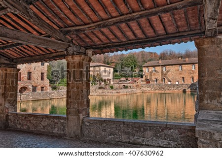 Bagno Vignoni, Siena, Tuscany, Italy: old thermal baths in the medieval village, view from the portico of the square of sources, spa basin in the ancient italian town
