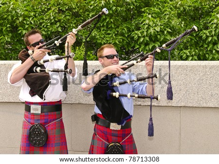 Bagpipe duo wearing kilts and having fun  between songs as they entertain tourists in Ottawa, Canada. - stock photo