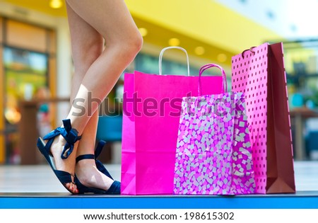 bags on the stairs in shopping mall next to woman legs - stock photo