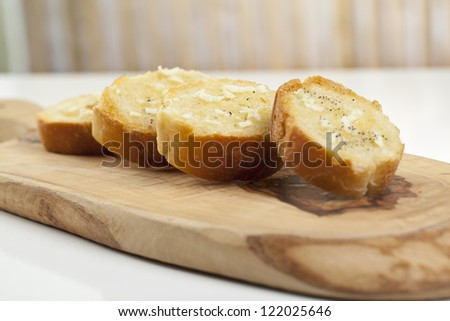 Baguette slices with garlic spread on top of a wooden chopping board - stock photo