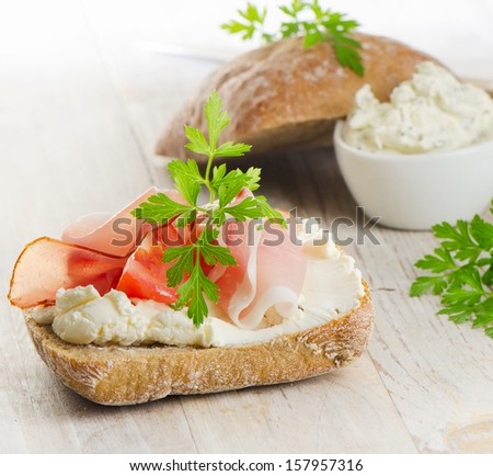 Baguette with bacon and cream cheese with herbs. Selective focus - stock photo