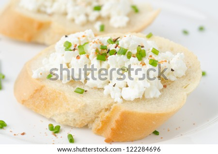 baguette with cottage cheese and green onion on a plate - stock photo