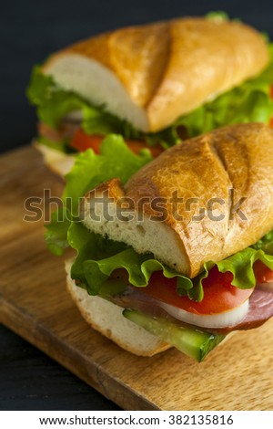 Baguette with ham, vegetable slices and lettuce on wooden table. Fast food - stock photo
