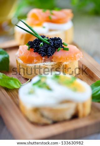 baguette with smoked salmon, caviar and eggs - stock photo