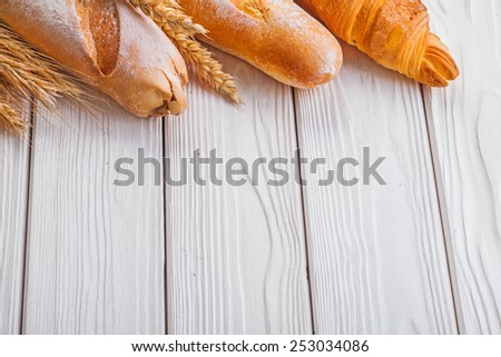 baguettes and croissant wheat ears on wooden boards with copyspace   - stock photo