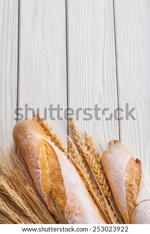 baguettes and ears of wheat on old white wooden boards with copyspace vertical version  - stock photo