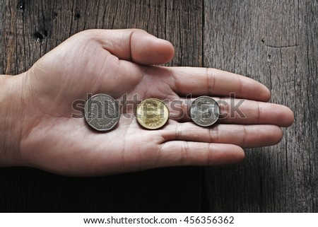 Baht Thailand coins on hand on a wooden table.
