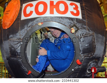 BAIKONUR, KAZAKHSTAN - NOVEMBER 12, 2014: ISS Expedition 42-43 NASA flight engineer Terry Virts looks out from the hatch of the Russian Soyuz TMA-15M spacecraft during fit check at Baikonur Cosmodrome - stock photo