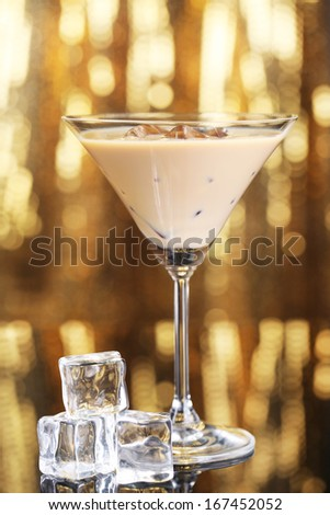 Baileys liqueur in glass on golden background - stock photo